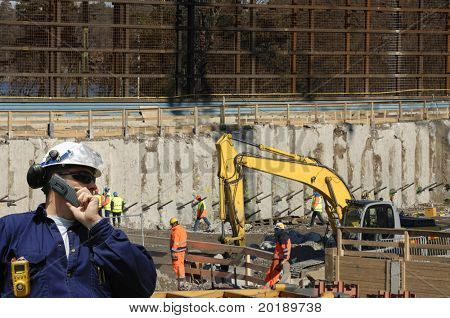 engineer in hard-hat supervising workers and bulldozers inside construction-site