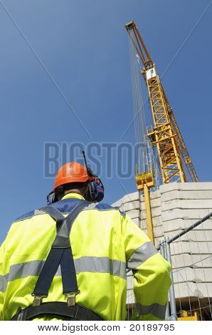 engineer in hard-hat looking up at large mobile crane