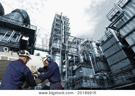 oil refinery, pipelines and engineers, background in a blue toning concept