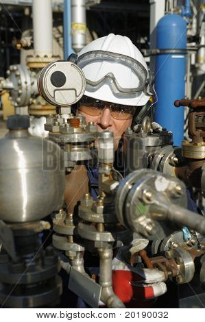 engineer working behind oil and gas pipes inside control-room of refinery