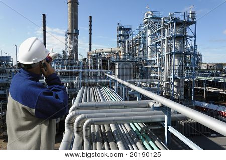 oil-worker in foreground pointing at oil and gas refinery in background