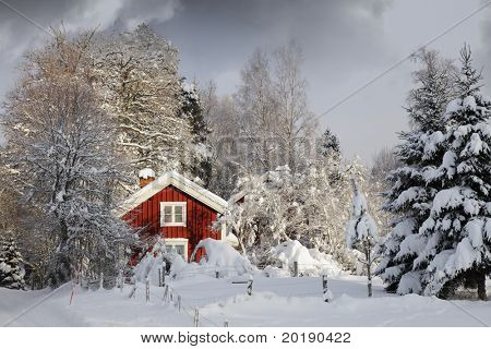 small red cottagein winter, snow and ice scenery, smaland, sweden