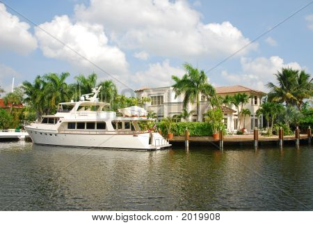 Yacht Docked Behind Luxury Home