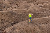 Man trail running in the mountain hills nature landscape. Ultra runner competing on cross country ra poster