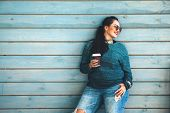 Beautiful woman wearing fall sweater, ripped jeans and glasses drinking take away coffee standing ag poster