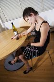 picture of saddening  - woman sitting with bowed head and wine bottle - JPG