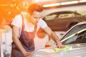 Young automobile mechanic cleaning car in repair shop poster