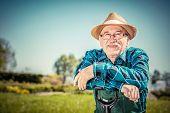 Portrait of a senior gardener standing in a garden with a shovel. Gardening poster