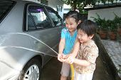 stock photo of car wash  - Kids washing car in a sunny afternoon happily - JPG