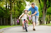 Happy Father Teaching His Little Daughter To Ride A Bicycle. Child Learning To Ride A Bike. poster