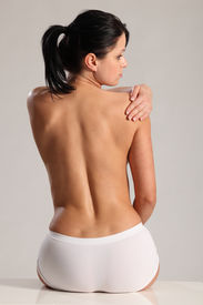 stock photo of knickers  - Beautiful young woman wearing white knickers with a naked back reaching over to massage shoulder pain - JPG