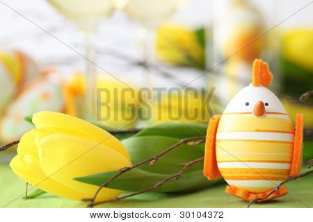 Closeup of easter egg and yellow tulip on table.