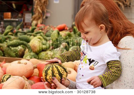 Mother Showing Daughter A Gourd At A Market