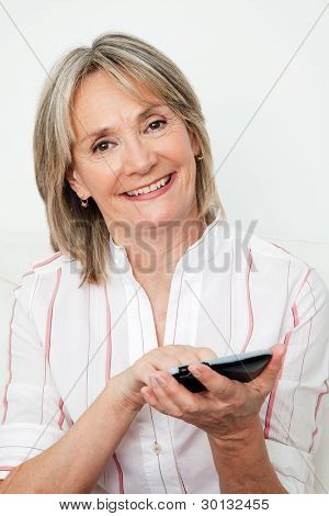 Happy senior woman using smartphone with touchscreen