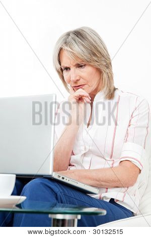Mulher sênior frustrada com o laptop em casa no sofá