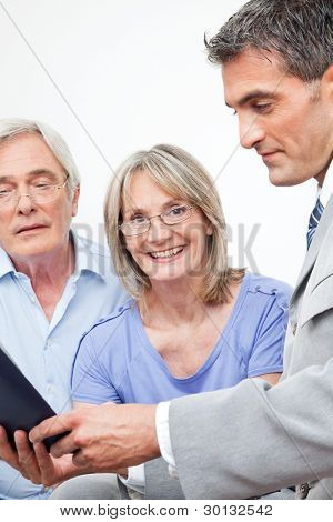 Happy senior woman with her husband at home with financial advisor