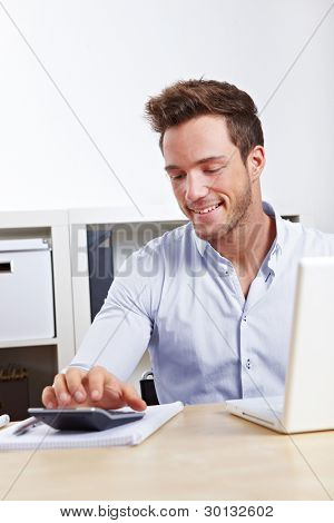 Happy Business man with laptop using calculator