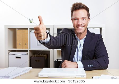 Successful business man in office holding his thumbs up