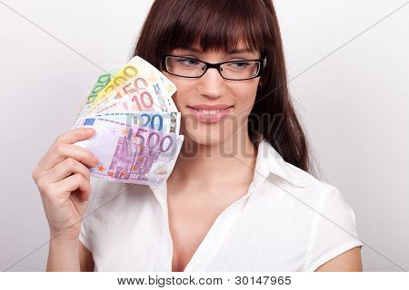Young Woman Daydreaming With Money In Her Hands