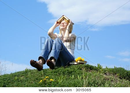Female Student Outdoor On Green Grass With Books And Blue Sky In Background