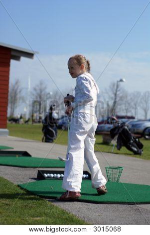 Female Golfer Playing On A Golf Course