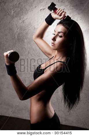 high contrast portrait of a  beautiful young woman working out with dumbbells in the gym