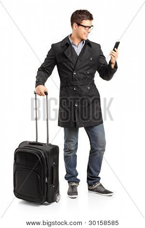 Full length portrait of a young man prepared for a yourney typing a sms isolated on white background