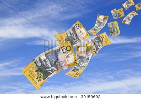 Australian fifty dollar bills falling from a blue sky.