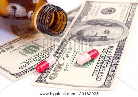 Pills and empty bottle on the hundred-dollar bills