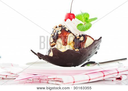 Vanilla Ice With Caramel, Chocolate Sauce, Nuts And Cherry In A Bowl From Chocolate On White Backgro