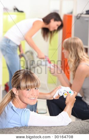 Three female roommates playing video game.