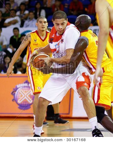 KUALA LUMPUR - FEBRUARY 19: Malaysian Dragons' Brian Williams (white) dribbles in at the ASEAN Basketball League match against Singapore Slingers on Feb 19, 2012 in Kuala Lumpur, Malaysia.  Dragons won 86-71.