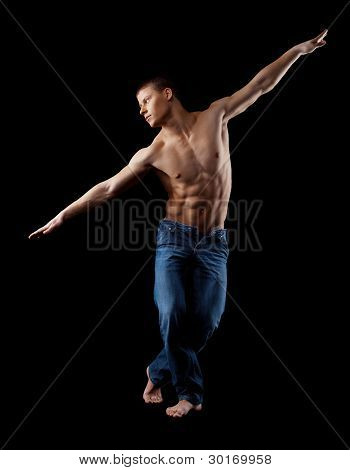 man with naked torso in jeans posing in dark
