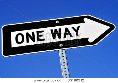 a one way sign over the blue sky