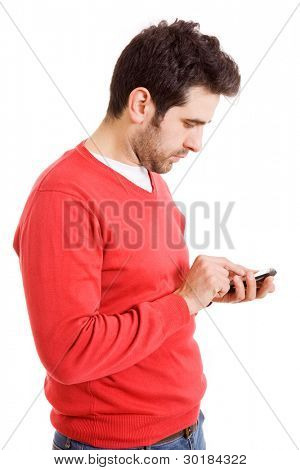 Portrait of a young boy text messaging on mobile phone against white background