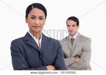 Vendedora con los brazos cruzados y colega detrás de ella contra un fondo blanco