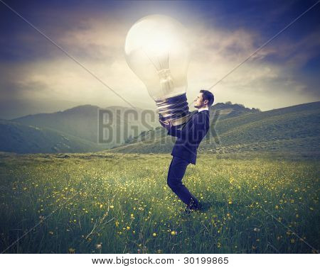 Businessman lighting up a green meadow with a giant light bulb