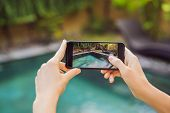Hand Holding Phone On Background Of The Pool In Hotel. Photo Camera On The Screen. Close Up Hand Hol poster