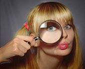 stock photo of pulling hair  - Girl and magnifying glass looking at camera green eyes funny