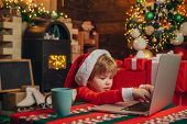 Santa Little Helper. Little Boy Santa Hat And Costume Having Fun. Boy Child With Laptop Near Christm poster