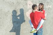 Happy Dad Is Holding A Daughter. Shadow Of Dad And Daughter On The Wall. On The Wall The Inscription poster