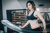 Attractive Muscular Smiling Fitness Woman Running On Treadmill In Gym poster
