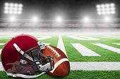 Close Up Of American Football Helmet And Ball On Stadium Field With Yard Line Markings And Spotlight poster