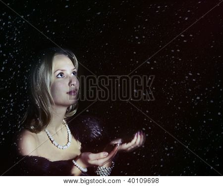 Portrait of blonde girl with falling snow on