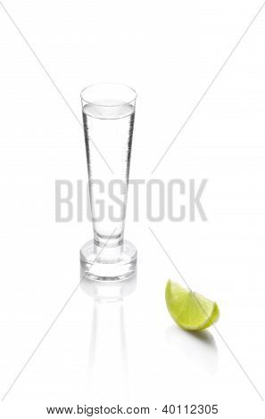 Shot Glass Filled With Clear Cold Alcohol Isolated On White