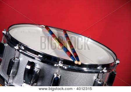 Silver Sparkel Snare Drum And Sticks Isolated On Red
