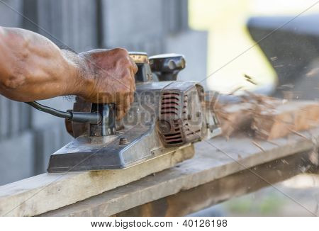 Carpenter Working With Electric Planer