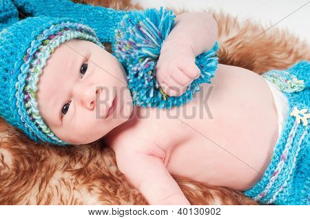 Newborn baby in long blue knitted hat
