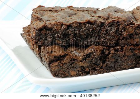 Two Vegan Brownies On A White Plate