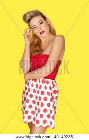 Modelo de moda retro rubia glamorosa en una minifalda roja lunares con lápiz labial rojo vivo y un viejo